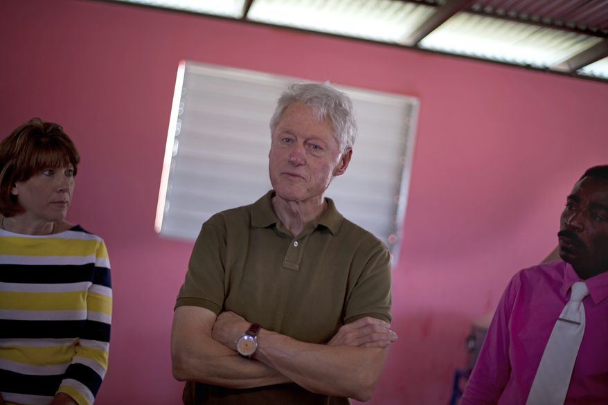 Former U.S. President and UN special envoy to Haiti Bill Clinton listens to members of the Union Des Apotres – Prodev School in Cite Soleil, Port-au-Prince, Haiti, Monday Feb. 17, 2014. Clinton is in Haiti to visit several projects that focus on agriculture and the environment, including the Union Des Apotres – Prodev solar-powered school that his private foundation has assisted and a training school for Haitian coffee farmers. (AP Photo/Dieu Nalio Chery)(AP Photo/Dieu Nalio Chery)