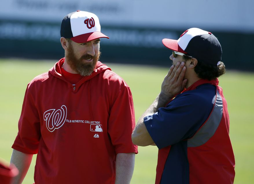 Washington Nationals first baseman Adam LaRoche, left, talks with second baseman Anthony Rendon during a spring training baseball workout, Monday, Feb. 17, 2014, in Viera, Fla. (AP Photo/Alex Brandon)