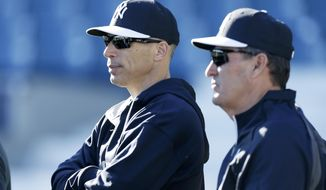 New York Yankees manager Joe Girardi, left, and Yankees' director of player development Pat Roessler watch a pitcher throw during spring training baseball practice Tuesday, Feb. 18, 2014, in Tampa, Fla. (AP Photo/Charlie Neibergall)