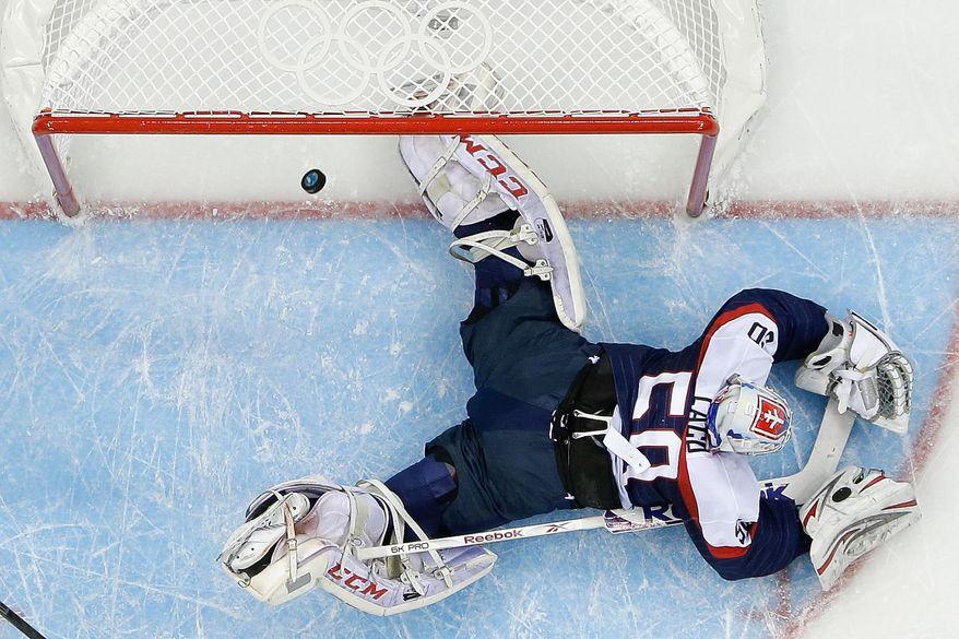 Czech Republic forward Roman Cervenka shot flies past Slovakia goaltender Jan Laco during the first period of the 2014 Winter Olympics men's ice hockey game at Shayba Arena, Tuesday, Feb. 18, 2014, in Sochi, Russia. (AP Photo/Matt Slocum)
