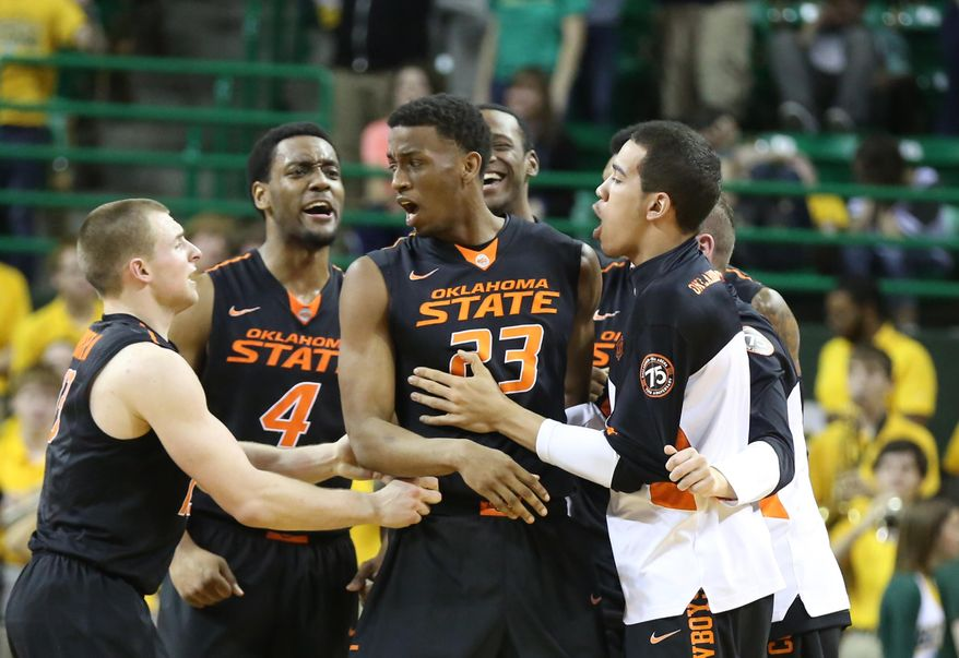 Oklahoma State players grab forward Leyton Hammonds (23) after sending their game against Baylor to overtime in an NCAA college basketball game, Monday, Feb. 17, 2014, in Waco, Texas.  Baylor won 70-64. (AP Photo/Waco Tribune Herald, Rod Aydelotte)