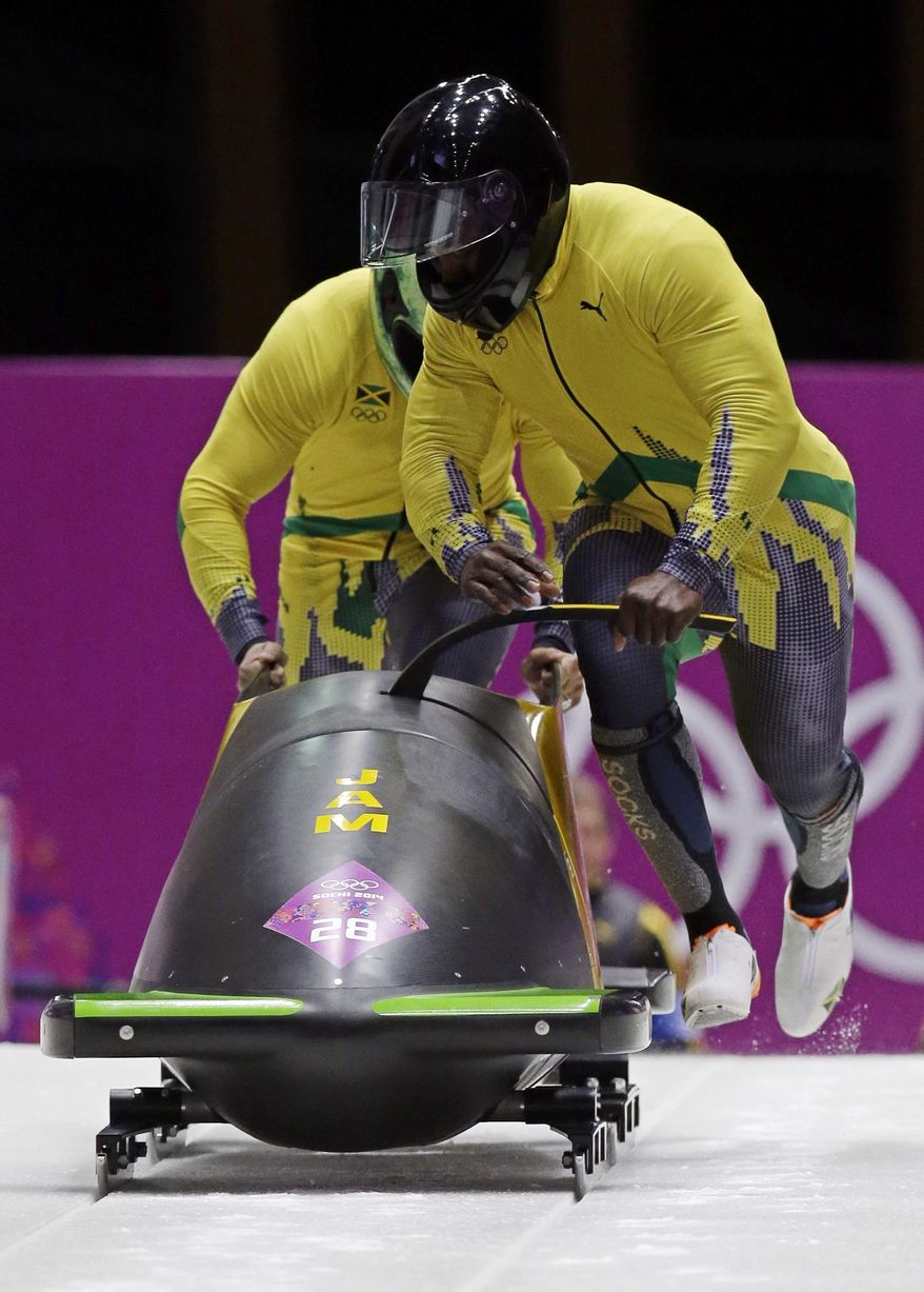 The team from Jamaica JAM-1, piloted by Winston Watts and brakeman Marvin Dixon, start their third run during the men's two-man bobsled competition at the 2014 Winter Olympics, Monday, Feb. 17, 2014, in Krasnaya Polyana, Russia. (AP Photo/Michael Sohn)