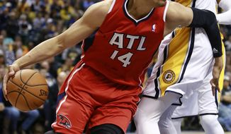 Atlanta Hawks center Gustavo Ayon (14) works his way around Indiana Pacers center Roy Hibbert during the first half of an NBA basketball game in Indianapolis, Tuesday, Feb. 18, 2014. (AP Photo/R Brent Smith)