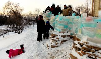 In this February 2014 photo provided by Gary Pruitt, people gather around the completed ice castle Pruitt created at his home St. Paul, Minn. The ice castle was vandalized Feb. 15 by two kids, according to Pruitt who said said he saw them using golf clubs to destroy the structure that was 10 feet high, 50 feet long and made of about 700 blocks of ice. The ice castle, which took two months to build, was made from ice bricks using shoeboxes and milk jugs filled with water mixed with food coloring. (AP Photo/Gary Pruitt)