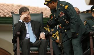 In this Thursday, Feb. 13, 2014, photo, Army Commander Gen. Juan Pablo Rodriguez, right, talks to Colombia's President Juan Manuel Santos, during a military ceremony in Bogota, Colombia. Santos announced that changes on the military chain of command will be decided Tuesday, Feb. 18, 2014, after the country's leading newsmagazine, Semana, reported on what it called widespread kickbacks in multimillion-dollar military contracts, and the publication online of an audio recording in which Gen. Leonardo Barrero, the armed forces chief, is heard verbally maligning prosecutors' investigations into the extrajudicial killings that have brought Colombia international reproach. (AP Photo/Fernando Vergara)