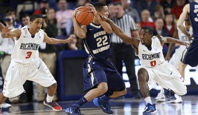 Richmond's ShawnDre' Jones (3) and Kendall Anthony (0) defend George Washington's Joe McDonald (22) during the first half of an NCAA college basketball game Tuesday, Feb. 18, 2014, in Richmond, Va. (AP Photo/Richmond Times-Dispatch, Mark Gormus)