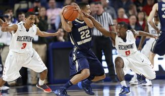 Richmond's ShawnDre' Jones (3) and Kendall Anthony (0) defend George Washington's Joe McDonald (22) during the first half of an NCAA college basketball game Tuesday, Feb. 18, 2014, in Richmond, Va. (AP Photo/Richmond Times-Dispatch, Mark Gormus)