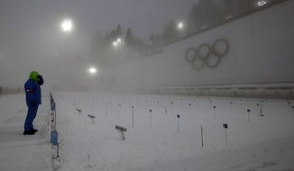 A race officer checks visibility from the shooting range, prior to the men's biathlon 15k mass-start, at the 2014 Winter Olympics, Tuesday, Feb. 18, 2014, in Krasnaya Polyana, Russia. (AP Photo/Lee Jin-man)