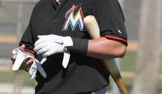 Miami Marlins catcher Jarrod Saltalamacchia looks out onto the field during spring training baseball practice, Monday, Feb. 17, 2014 at Roger Stadium in Jupiter, Fla. (AP Photo/El Nuevo Herald, Hector Gabino)
