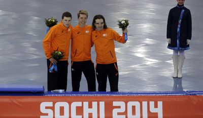 Athlethes from the Netherlands, from left to right, silver medallist Sven Kramer, gold medallist Jorrit Bergsma, and bronze medallist Bob de Jong poses for photographers during the flower ceremony for the men's 10,000-meter speedskating race at the Adler Arena Skating Center during the 2014 Winter Olympics in Sochi, Russia, Tuesday, Feb. 18, 2014. (AP Photo/Matt Dunham)
