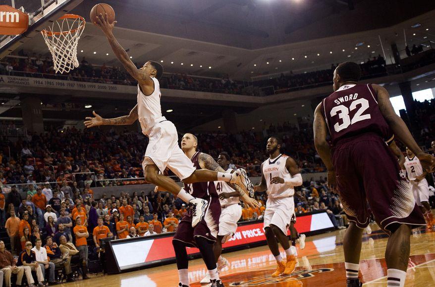 Auburn's Chris Denson (3) hits a layup as Mississippi State's Colin Borchert (3) looks on during an NCAA college basketball game Saturday, Feb. 15, 2014, at Auburn Arena in Auburn, Ala. (AP Photo/The Opelika-Auburn News, Albert Cesare)
