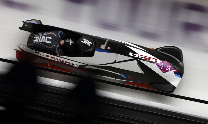 The team from the United States USA-1, piloted by Steven Holcomb and brakeman Steven Langton, take a turn during the men's two-man bobsled competition at the 2014 Winter Olympics, Monday, Feb. 17, 2014, in Krasnaya Polyana, Russia. (AP Photo/Michael Sohn)