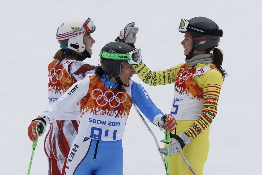 Lithuania's Ieva Januskeviciute, left, Greece's Sophia Ralli , center, and Togo's Alessia Afi Dipol, right, celebrate after completing the first run in the women's giant slalom at the Sochi 2014 Winter Olympics, Tuesday, Feb. 18, 2014, in Krasnaya Polyana, Russia. (AP Photo/Christophe Ena)