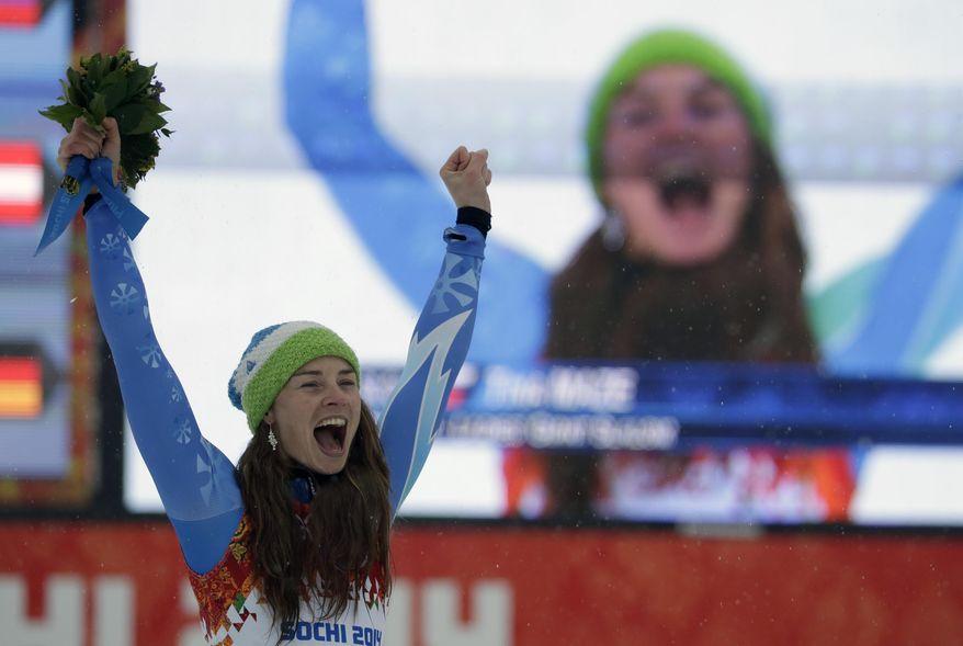 Women's giant slalom gold medal winner Tina Maze of Slovenia celebrates on the podium during a flower ceremony at the Sochi 2014 Winter Olympics, Tuesday, Feb. 18, 2014, in Krasnaya Polyana, Russia. (AP Photo/Gero Breloer)