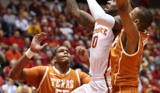 Iowa State guard DeAndre Kane goes past Texas' Cameron Ridley and Demarcus Holland, right, during the first half of an NCAA college basketball game at Hilton Coliseum in Ames, Iowa, Tuesday, Feb. 18, 2014. Iowa State won 85-76. (AP Photo/Justin Hayworth)