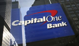 **FILE** New York buildings are reflected in the window of a Capital One bank office window on April 25, 2008. (Associated Press)
