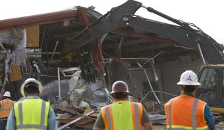 This undated photo provided by the Fort Hood Public Affairs Office shows Building 42003 being demolished in Fort Hood, Texas. Fort Hood officials said Tuesday, Feb. 18, 2014, that they have torn down Building 42003, the site of a 2009 massacre that left 13 people dead and more than 30 wounded. They plan to place trees, a gazebo and a memorial plaque at the site.(AP Photo/Fort Hood Public Affairs Office)