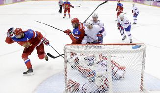 Russia forward Ilya Kovalchuk, left, reacts after  scoring against Norway goaltender Lars Haugen for a goal in the second period of a men's ice hockey game at the 2014 Winter Olympics, Tuesday, Feb. 18, 2014, in Sochi, Russia. (AP Photo/Mark Humphrey)