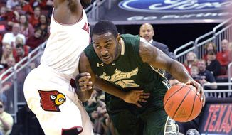 South Florida's Shemiye McLendon, right, attempts to drive around the defense of Louisville's Chris Jones during the first half of an NCAA college basketball game, Tuesday, Feb. 18, 2014, in Louisville, Ky. (AP Photo/Timothy D. Easley)