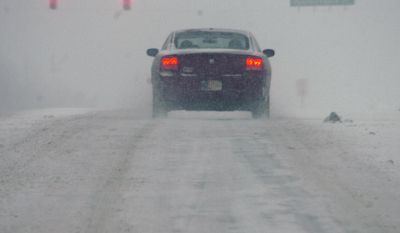 A motorist waits at stop light as snow falls Monday, Feb. 17, 2014, on Ind. 18 east of Marion, Ind. (AP Photo/The Chronicle-Tribune, Jeff Morehead)
