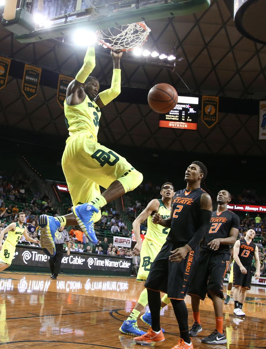 Baylor forward Cory Jefferson (34) dunks past Oklahoma State guard/forward Le'Bryan Nash (2), right, in the second half of an NCAA college basketball game, Monday, Feb. 17, 2014, in Waco, Texas. Baylor won 70-64 in overtime. (AP Photo/Waco Tribune Herald, Rod Aydelotte)