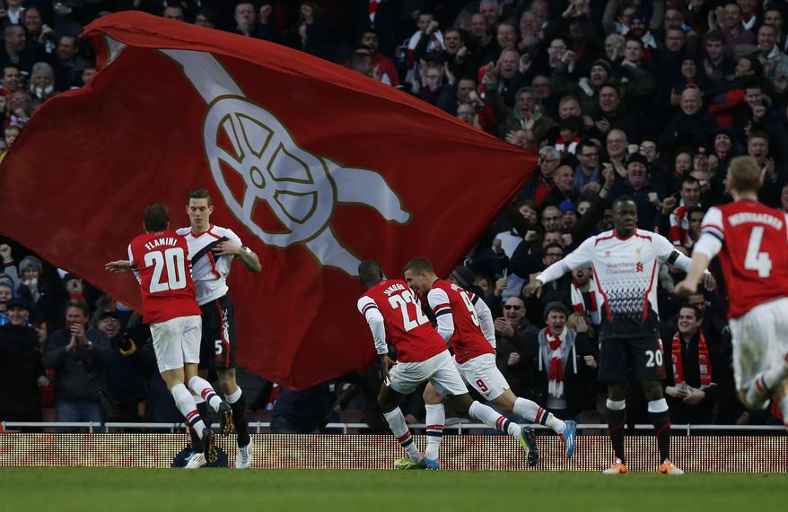 Arsenal's Lukas Podolski, center right, celebrates his goal against Liverpool with teammates during their English FA Cup fifth round soccer match at Emirates Stadium in London, Sunday, Feb. 16, 2014. (AP Photo/Sang Tan)