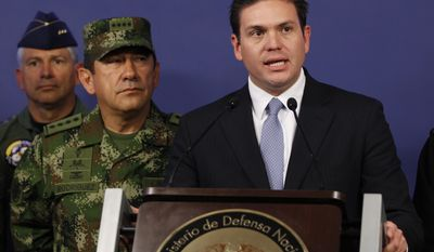 Colombia's Defense Minister Juan Carlos Pinzon, right, speaks as the new chief of the armed forces Gen. Juan Pablo Rodriguez looks on during a press conference in Bogota, Colombia, Tuesday, Feb. 18, 2014. Pinzon named Rodrigues for the post after firing former chief Gen. Leonardo Barrero for verbally maligning prosecutors' investigations into the extrajudicial killings that have brought Colombia international reproach. (AP Photo/Fernando Vergara)