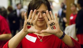 Beth Roth shows off messages written on her hands in opposition to a bill seeking to allow wedding vendors to deny services for same-sex ceremonies that was withdrawn in Senate committee in Nashville, Tenn., on Tuesday, Feb. 18, 2014. The measure sponsored by Republican Sen. Mike Bell of Riceville was pulled from the Senate Judiciary Committee. (AP Photo/Erik Schelzig)