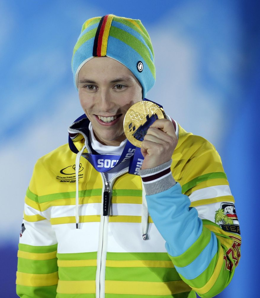 Men's normal hill nordic combined gold medalist Eric Frenzel of Germany poses with his medal during the medals ceremony at the 2014 Winter Olympics, Thursday, Feb. 13, 2014, in Sochi, Russia. (AP Photo/Morry Gash)