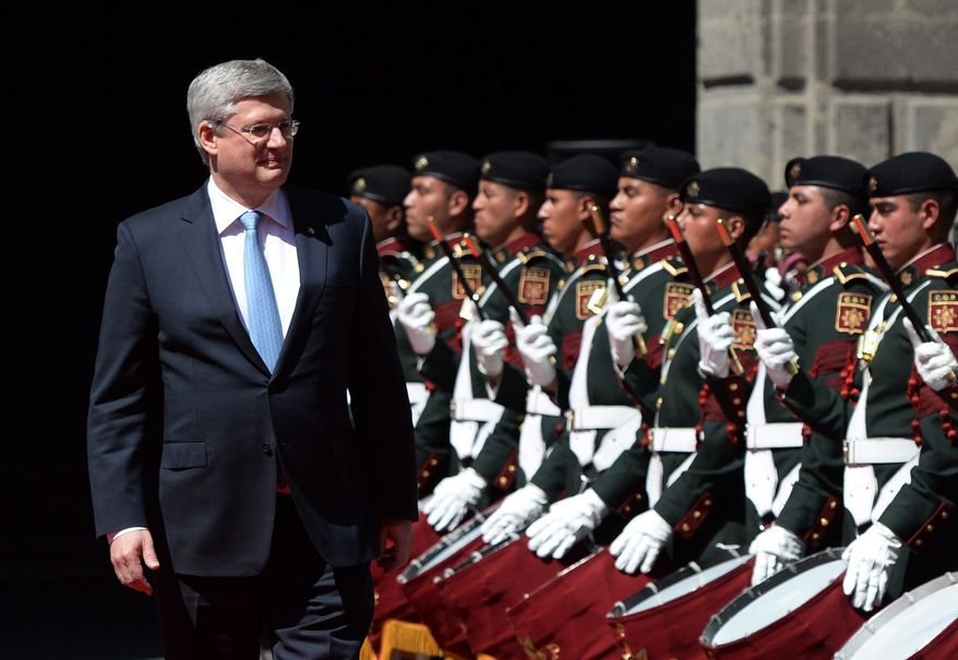 Canada's Prime Minister Stephen Harper walks past the honor guard as he arrives at the National Palace in Mexico City, Tuesday, Feb. 18, 2014. (AP Photo/The Canadian Press, Sean Kilpatrick)