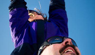 Jim Bassett of Saranac, N.Y. and her daughter Paige, 8, watch a plane fly over head at Gravely Point Park, Arlington, Va., Tuesday, February 18, 2014. (Andrew Harnik/The Washington Times)