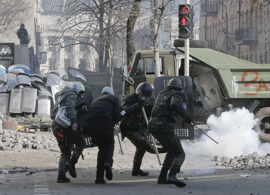 Anti-government protesters clashed with riot police outside Ukraine's parliament in Kiev, Ukraine, Tuesday, Feb. 18, 2014. Ukraine's political crisis escalated sharply Tuesday, with at least nine people reported killed and scores injured in violent, often fiery battles between anti-government demonstrators and police in Kiev. The clashes outside parliament erupted after the opposition accused the government of ignoring its demands even after nearly three months of protests that have paralyzed the capital. It was the worst violence since the protests began in late November.(AP Photo/Efrem Lukatsky)