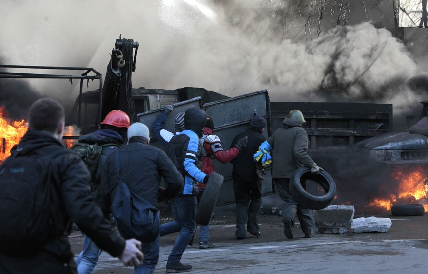 Anti-government protesters clash with riot police outside Ukraine's parliament in Kiev, Ukraine, Tuesday, Feb. 18, 2014. Thousands of angry anti-government protesters clashed with police in a new eruption of violence Tuesday.(AP Photo/Sergei Chuzavkov)