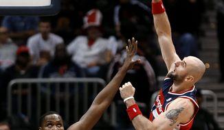 Washington Wizards center Marcin Gortat (4) shoots over Atlanta Hawks forward Elton Brand (42) during the first half of an NBA basketball basketball game Wednesday, Feb. 19, 2014, in Atlanta.   (AP Photo/John Bazemore)
