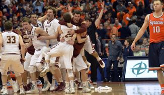 Boston College players celebrate after defeating Syracuse 62-59 in overtime as Syracuse's Trevor Cooney, right, walks off the court following an NCAA college basketball game in Syracuse, N.Y., Wednesday, Feb. 19, 2014. (AP Photo/Kevin Rivoli)