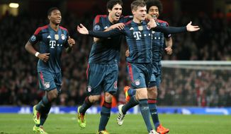 Munich's Toni Kroos, front celebrates his side's opening goal with David Alaba, Javier Martinez and Dante, from left,  during a Champions League, round of 16, first leg soccer match between Arsenal and Bayern Munich at the Emirates stadium in London, Wednesday, Feb. 19, 2014 .(AP Photo/Alastair Grant)