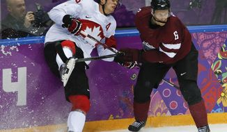 Latvia defenseman Arvids Rekis checks Canada forward Jonathan Toews during the second period of a men's quarterfinal ice hockey game at the 2014 Winter Olympics, Wednesday, Feb. 19, 2014, in Sochi, Russia. (AP Photo/Mark Humphrey)