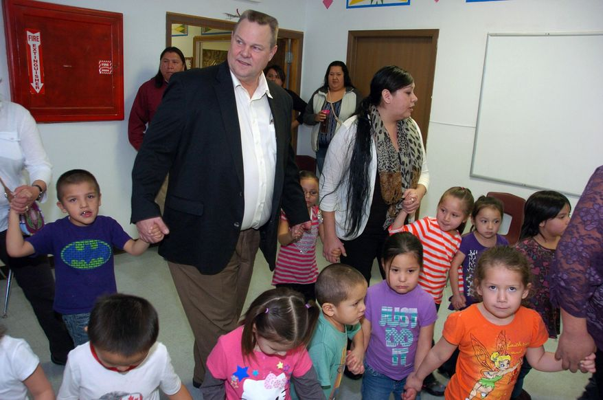 U.S. Sen. Jon Tester, center, dances around a drum circle with students at the Head Start early education center in Crow Agency, Mont., on Wednesday, Feb. 19, 2014. Tester is the new chairman of the U.S. Senate Indian Affairs Committee and says he'll use his new role as chairman to target wasteful spending, improve educational opportunities and promote job development on reservations. (AP Photo/Matthew Brown)