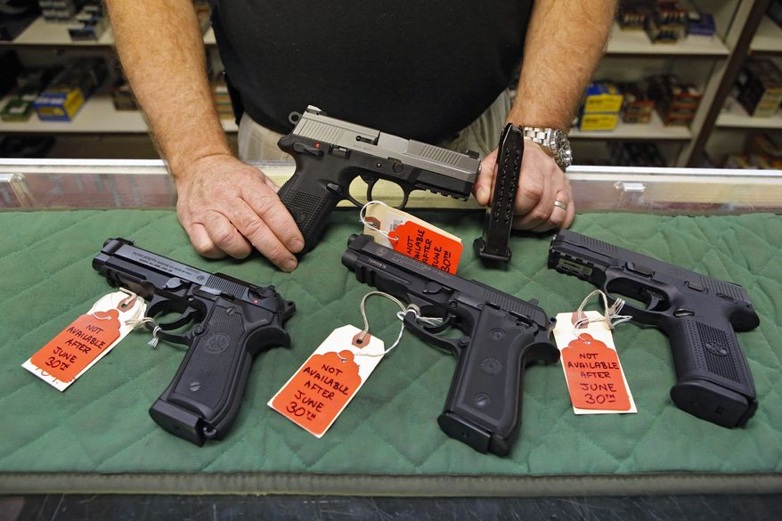 ** FILE ** In this photo taken on Thursday, June 27, 2013, Richard Taylor manager of at Firing-Line gun store in Aurora, Colo., shows some of the pistols that he won't be able to sell after June 30, 2013, because their magazines hold more than 15 rounds. (AP Photo/Ed Andrieski)