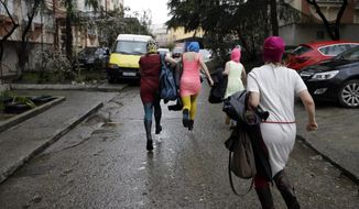 Russian punk group Pussy Riot members Nadezhda Tolokonnikova, in the blue balaclava, and Maria Alekhina, in the pink balaclava, run down the street with other women after they were released from a police station, Tuesday, Feb. 18, 2014, in Adler, Russia. No charges were filed against Tolokonnikova and Alekhina along with the others who were detained. (AP Photo/Morry Gash)
