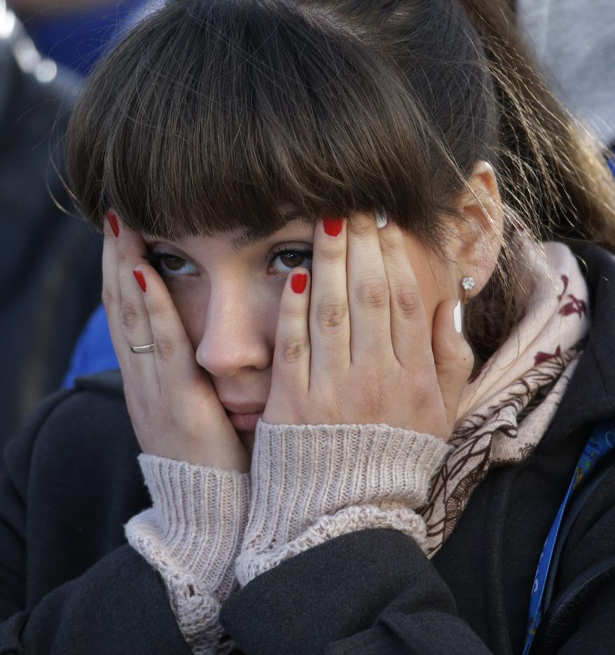 A fan covers her face while watching the men's ice hockey game between Russia and Finland on a large screen in Olympic Park, at the 2014 Winter Olympics, Wednesday, Feb. 19, 2014, in Sochi, Russia. (AP Photo/Morry Gash)