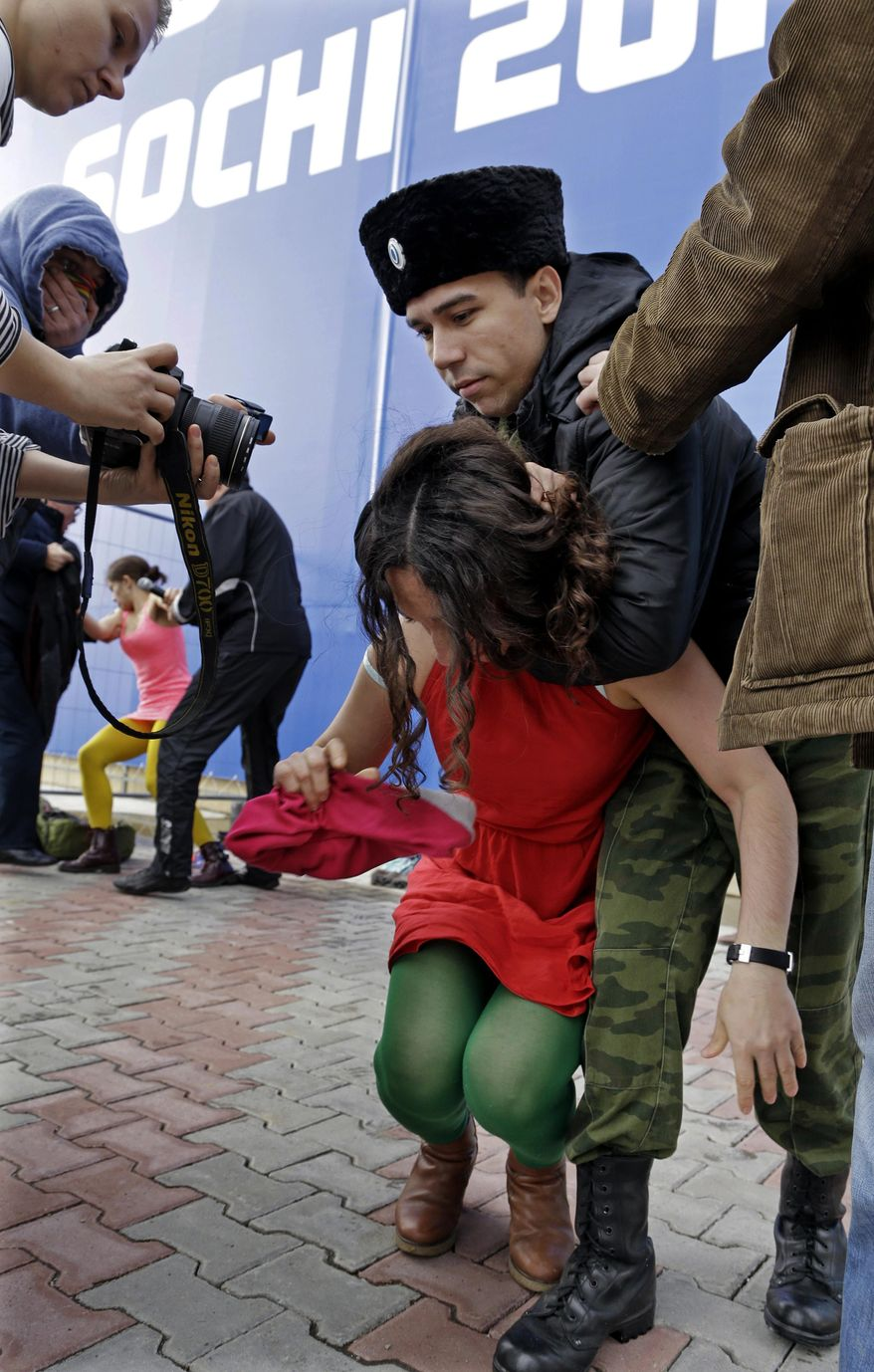 A member of the punk group Pussy Riot is restrained by a member of the Cossack militia  in Sochi, Russia, on Wednesday, Feb. 19, 2014. Cossack militia attacked the Pussy Riot punk group with horsewhips on Wednesday as the group tried to perform under a sign advertising the Sochi Olympics. The group had gathered to perform in a downtown Sochi restaurant, about 30km (21miles) from where the Winter Olympics are being held.They left the restaurant wearing bright dresses and ski masks and had only been performing for a few seconds when they were set upon by Cossacks. (AP Photo/Morry Gash)
