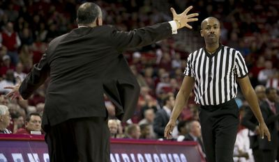 South Carolina head coach Frank Martin, left, yells at referee James Barker, right, during the first half of an NCAA college basketball game, Wednesday, Feb. 19, 2014, in Fayetteville, Ark. (AP Photo/Gareth Patterson)