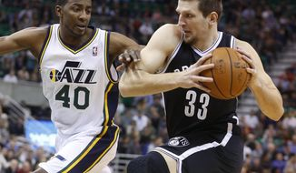 Brooklyn Nets forward Mirza Teletovic (33), of Bosnia, drives while defended by Utah Jazz forward Jeremy Evans (40) during the first half of an NBA basketball game Wednesday, Feb. 19, 2014, in Salt Lake City. (AP Photo/Jim Urquhart)