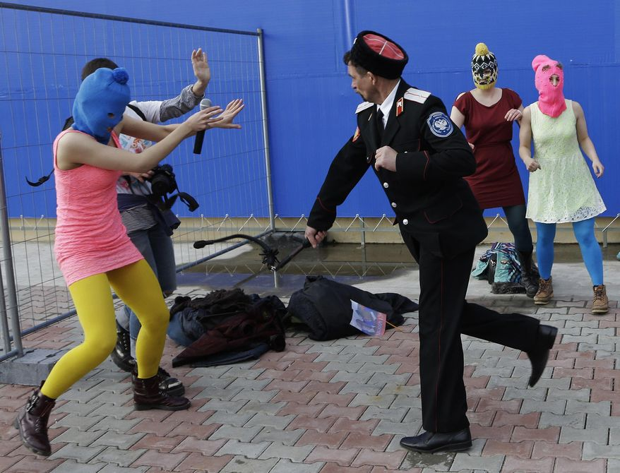 A Cossack militiaman attacks Nadezhda Tolokonnikova and a photographer as she and fellow members of the punk group Pussy Riot, including Maria Alekhina, right, in the pink balaclava, stage a protest performance in Sochi, Russia, on Wednesday, Feb. 19, 2014. The group had gathered in a downtown Sochi restaurant, about 30km (21miles) from where the Winter Olympics are being held. They ran out of the restaurant wearing brightly colored clothes and ski masks and were set upon by about a dozen Cossacks, who are used by police authorities in Russia to patrol the streets. (AP Photo/Morry Gash)