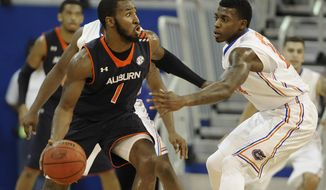 Auburn guard KT Harrell (1) tries to get past Florida forward Casey Prather (24) during the first half of an NCAA college basketball game Wednesday Feb. 19, 2014 in Gainesville, Fla. (AP Photo/Phil Sandlin)