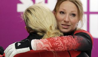 The team from Canada CAN-1, piloted Kaillie Humphries with brakeman Heather Moyse, hug after their third run during the women's bobsled competition at the 2014 Winter Olympics, Wednesday, Feb. 19, 2014, in Krasnaya Polyana, Russia. (AP Photo/Natacha Pisarenko)