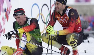 Germany's Hannes Dotzler and Tim Tscharnke, left, sit in the finish area after the men's cross-country team sprint competitions at the 2014 Winter Olympics, Wednesday, Feb. 19, 2014, in Krasnaya Polyana, Russia. (AP Photo/Matthias Schrader)