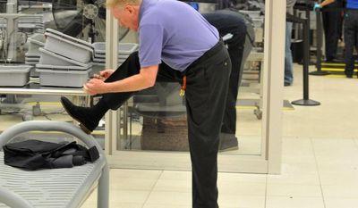 **FILE** A traveler removes his shoes at Hartsfield-Jackson Atlanta International Airport on Jan. 15, 2014. (Associated Press/Atlanta Journal-Constitution)