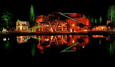 FILE - In this Feb. 8, 2014 file photo, the orange-lit Holland Heineken House is reflected in a pond following the appearance of gold medalist Sven Kramer of the Netherlands on stage in front of fans after he set a new Olympic record to win the 5,000-meter speedskating race at the 2014 Winter Olympics in Sochi, Russia. With Dutch speedskaters dominating the 2014 Winter Olympics like never before, the Holland House has become the house of champions. (AP Photo/Matt Dunham, File)